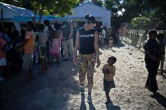 Katy Perry walks with a small boy she has just met during her visit to the Tamatave Youth Center in the city of Tamatave in Atsinanana Region. The center supports recreational activities for adolescents.