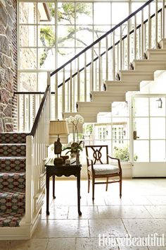 The addition of a dramatic two-story glass wall behind the floating back stairway floods the space with sunlight.