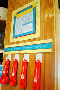 Get a few self-adhesive hooks to make an easy-grab station for your measuring spoons.