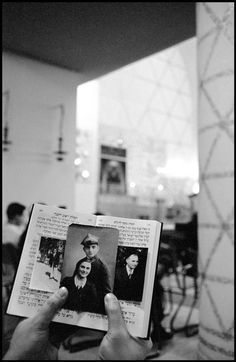 Leonard Freed West Germany. Frankfurt am Main. 1961. In a synagogue, a worshipper shows portraits of his family killed in the concentration camps.