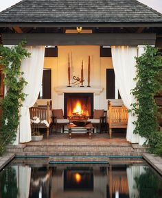 the shuttered windows at rear wall, the white drapes, the vines, the fireplace, the brick flooring