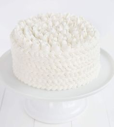 Cake covered in white buttercream with a russian tip roses on top!
