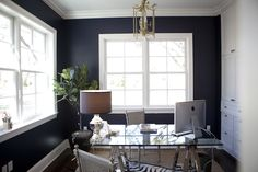 Chic navy blue home office with polished nickel sawhorse desk topped with a mercury glass urn shaped lamp, with a pair of French cane chairs across from one another below a gold pagoda chandelier over hardwood floors layered with a braided jute rug topped with a zebra hide.
