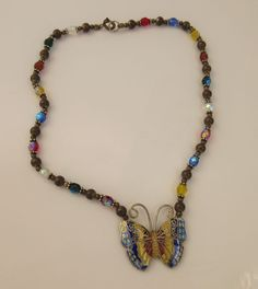Old vintage metal butterfly pendant on glass bead and metal necklace