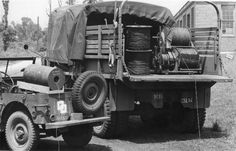 Image 22/30  1/4-ton truck (Willys MB jeep) and 2 1/2-ton 6x6 truck (CCKW) with wire and equipment for a four mile standardized military circuit.  The range of field wire circuits using sound powered telephones, it is 4 miles (6.4km).  Showing wire W-110-B (on reels) and reel unit RL-26-(), in the truck.  Wire WD-1()/TT in eight dispensers MX-306()/G in jeep.  Prepared by Signal Corps Engineering Laboratories, 28 August 1946.  Note Willys embossed on rear panel of the jeep.
