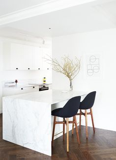 This pared back, considered, and exceptionally stylish Bellevue Hill home has a sleek kitchen with marble bench tops, white cabinetry, and fabric and timber stools.