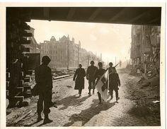 German Medics Surrender to 87th At Coblenz.  German medical aid men walk into a blasted building in Coblenz, where and 87th Division trooper waits to take them into captivity. Nazis took no chances and carried a huge Red Cross flag as they strolled to surrender.
