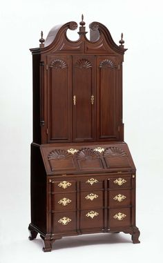 Desk & bookcase, 1770–1790, Providence, Rhode Island - Scroll pediment with carved finials. Triple division with convex & concave panels surmounted by carved shell forms on doors & slant lid, over 3 graduated blocked front drawers, on ogee feet. Doors flanked by fluted quarter columns. Brass bail handles & escutcheons. Often considered the apogee of early American cabinetmaking, Rhode Island desks & bookcases are notable for their superior craftsmanship & carved, block &  shell facades.