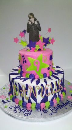 Justin Bieber is exploding out of the top of this cake in an explosion of stars