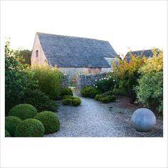 Gravel area featuring a stone sphere beside clipped box, Sarcococca, Rosa moyesii 'Geranium' and variegated Cornus - Coastal Garden, Dorset
