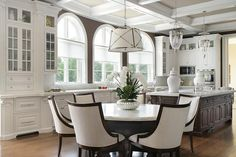 A Grosvenor Single Pendant hangs over a round marble top dining table lined with linen curved dining chairs.