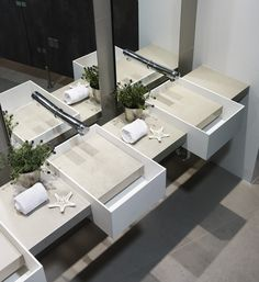 Restroom design mixes stone and whites with rectilinear basins for a sleek and  contemporary feel.