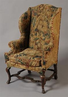 AN EARLY 18TH CENTURY WALNUT WING ARMCHAIR  The serpentine back and scrolled arms upholstered in 17th century tapestry fragments and later silk damask to the back, on cabriole legs with hoof feet joined by serpentine moulded stretchers, circa 1705