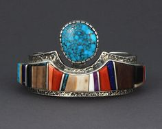 Sterling silver cuff bracelet with multi-stone inlay of coral, turquoise, lapis, sugilite, ironwood, and fossilized ivory and set with a Morenci turquoise cabochon by Wes Willie (Navajo)