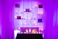 What a nice touch for the sweetheart table, a shelf wall with  pics of the bride and groom, mingled with candles.