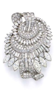 AN ART DECO DIAMOND BROOCH  Designed as pavé-set diamond scrolls and bombé swirls, with marquise and baguette-cut diamond openwork detail and trim, extending a larger marquise-cut diamond fringe, mounted in platinum, circa 1935