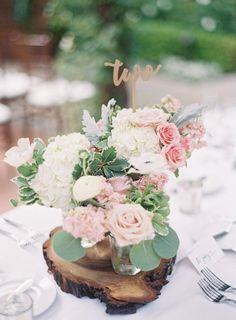 Elegant rustic table centerpieces with rose and white hydrangea in a mason jar on a tree stump tray: http://www.stylemepretty.com/california-weddings/san-juan-capistrano/2016/09/23/old-world-elegance-meets-garden-romance/ Photography: Sposto - http://spostophotography.com/