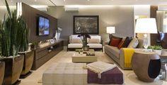 Cores claras, muita madeira, sofá grande e uma TV com bom tamanho foram colocados na sala de estar.