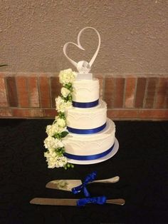 """3-tier wedding cake with our """"Arches and Dots"""" pattern set of beautifully with a royal blue ribbon and a cascade of white flowers. #wedding #weddingcakes #flowers"""
