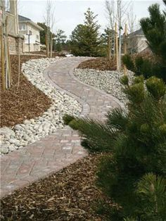 Brick garden pathways with mulch and stone alongside. Easy to care for, easy to walk on.