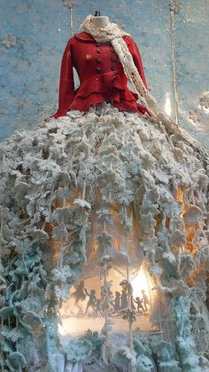 This Anthropologie Christmas window display fuses fashion and holiday spirit together. This red double breasted peacoat with a peplum is paired beautifully with a 3D snowflake skirt that blossoms out like crinoline. The inner skirt is raised, so that the silhouette of people merrily holding hands can be seen to symbolize unity.