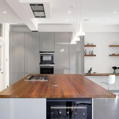 Mixed materials are still on trend. The natural timber tones and texture of this walnut worktop are the perfect foil for the subtle grey wall of the hi-gloss cabinetry behind.