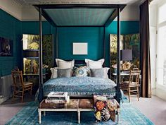 The bedroom with a four-poster bed with lots of cushions, and a bamboo chair, desk and screen either side