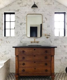 Dramatic marble tiled statement wall in handsome bathroom with black and white.