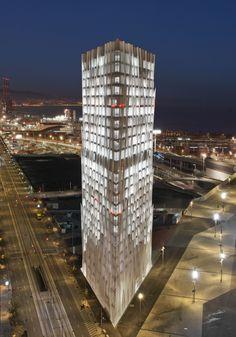 El edificio de 24 plantas y dos bajo rasante, obra del Estudio Massip-Bosch Arquitectes, con su perfil blanco en forma de rombo-diamante, tiene una gran amplitud y un aspecto ligero y luminoso, gracias al juego de penetración de luz entre las delgadas nervaduras de las fachadas.