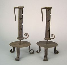 "Pair of wrought iron side ejector candlesticks, 19th c., with dished tripod base, 11 1/2"" h. Pook  Pook"