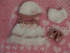 Hand knitted doll clothes for 5 Berenguer Bitty Baby / cupcake doll  Dress in white and pink 4 ply yarn with eyelash yarn hem and flower embellishments on bodice Fastens at back neck with metal popper  Matching panties shoes and hat.  All crafted in a smoke and pet free home  Doll not included