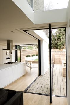 Open floorplan with wooden deck extending into the living room. Full glass doors that recede into the wall or pivot. Great way to open up a small space.