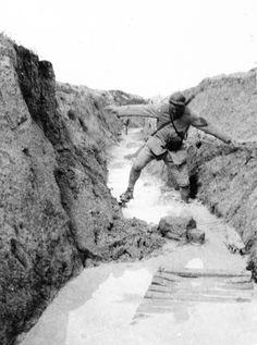 """""""Août 1917. Un agent de liaison dans un boyau inondé malgré la présence de caillebotis."""" Frantz Adam/AFP."""