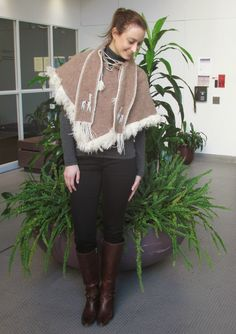 a second glance.: Llama-adorned poncho, grey turtleneck, black jeans, brown boots