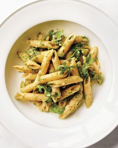 Penne Rigate with Arugula-Almond Pesto | Martha Stewart - Tomorrow is a big day for the cook, so make things easy tonight by letting someone else tackle dinner, or making something that's fast and a family favorite. We're thinking and tasting spring with this light and colorful pasta. #pennepasta #pesto #easydinner #easypasta