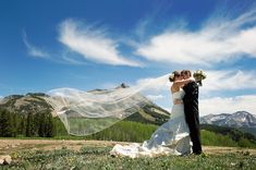The happy couple embracing in the middle of a field in front of the mountains under a blue sky,  photo by Adam Nyholt via junebugweddings.com