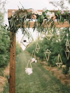 A wooden arch covered in delicate florals & hanging geometric figures | The Twins Photography