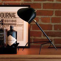 L'intemporelle lampe de bureau Tripode Mouille de coloris noir a été dessinée en 1955 par un des plus grands designers de luminaires du 20ème, Serge Mouille : une véritable icône de design qui habille élégamment un bureau ou une table de chevet...Un grand classique de la décoration contemporaine qui ne passe pas inaperçu.<br><br>Son corps est en acier, la rotule en laiton est pivotante à 270° et le réflecteur en aluminium est orientable à 55°. L'intérieur du réflecteur est blanc brillant…