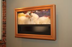 """Motorized artwork - """"When not in use, your television is disguised as a piece of elegant artwork. With the simple press of a button, your canvas painting quietly rolls up inside the frame to reveal your flat panel HDTV."""""""