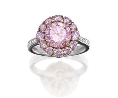 NATURAL FANCY PINK ARGYLE DIAMOND RING The round brilliant cut diamond weighing 2.50 carats is claw set surrounded by a cluster of fancy coloured diamonds of pink hue, to round brilliant cut diamond set shoulders and gallery, mounted in 18ct rose and white gold.
