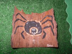 It is hard to see the beauty of this piece. It is painted on a piece of curved bark and gives a 3/D image to the spiders.