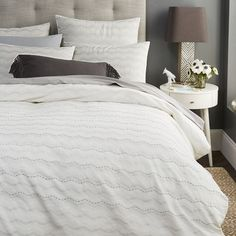 Set on an ivory cotton base, the Jacquard Zigzag Duvet Cover + Shams features alternating white and silver zigzag patterns. Rows of hand-stitched black thread interspersed in between add a bit of texture.