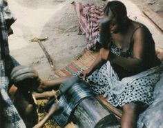 """Two Yoruba ladies beat an indigo dyed cloth to give it a glazed shiny finish, Nigeria, 1960s. Scanned from """"African Textiles"""" by Picton and Mack."""