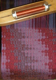 The structure is turned polychrome taquete. The warp is black, red, and purple. The black shows more on the other face of the cloth. Fine silk weft came from Lunatic Fringe in Tallahassee, Florida. By Bonnie Inouye.