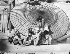 A yakonin with his servants under an enormous umbrella. Yokohama, ca. 1869-1870 by Wilhelm J. Burger