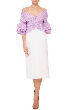 The Colombian fashion designer burst onto the scene with her eye-catchingly feminine aesthetic, crafted in conjunction with indigenous communities in her homeland. Crafted in a purple cotton gingham, this **Johanna Ortiz** top renders the wrap top entirely modern with ruched sleeves.