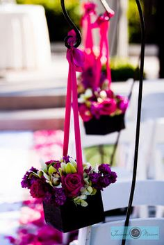 For a modern look, choose square boxes bursting with bright blooms. Hang them from simple posts with satin ribbon that matches your flowers.