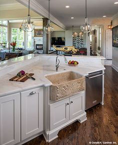 This kitchen island overlooks the dining room. The Monarch Manor house plan 5040. #WeDesignDreams