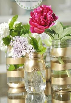 Sleek chic cheap glass vases not mason jars and candles not flowers.add a classy splash of metallic color to your home with quick and easy striped mason jars. Gold Mason Jars, Mason Jar Flowers, Painted Mason Jars, Flower Vases, Hanging Flowers, Diy Flowers, Spray Paint Mason Jars, Mason Jar Flower Arrangements, Mason Jar Sconce