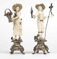 Pair German carved ivory & sterling table ornaments, 1913, Hanau, each with importer's mark for Berthold Hermann Muller, London & Chester, further marked ''925'' and with London import mark, the first modeled after a courtesan, the second a sheepherder, each carved ivory figure raised on a sterling silver platform over a waisted socle surmounting a domed silver-mounted rock crystal base, on paw feet.